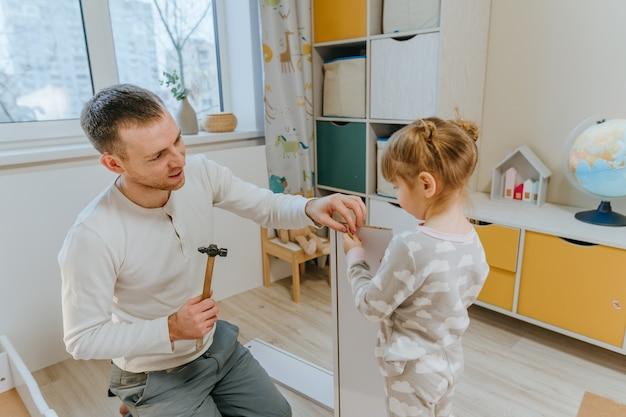 Een klein meisje van 4 jaar helpt haar vader met het monteren of repareren van de lade van het bed in de kinderkamer.