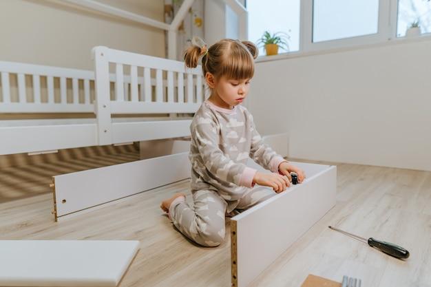 Een klein meisje van 4 jaar monteert de lade van het bed in de kinderkamer.