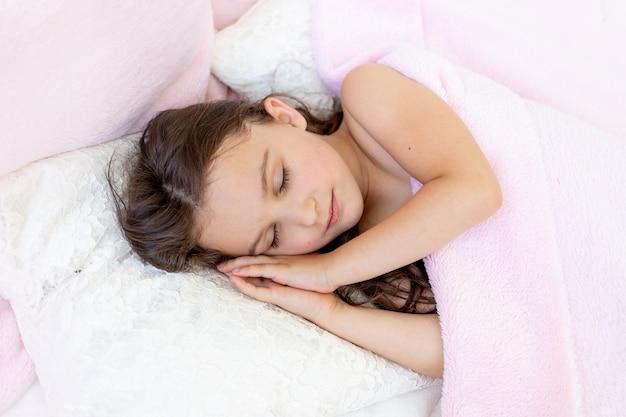 Een klein meisje van 5-6 jaar lacht in haar slaap, het kind ligt in bed met haar handen onder haar hoofd gevouwen