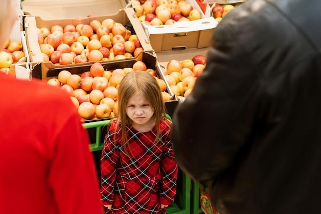 Een klein meisje van 5 jaar ziet er slecht uit naar mama en papa. verstoor hysterisch meisje met gesloten ogen die luid huilen terwijl het manipuleren van ouders en zich tegen voedselbox in supermarkt bevinden