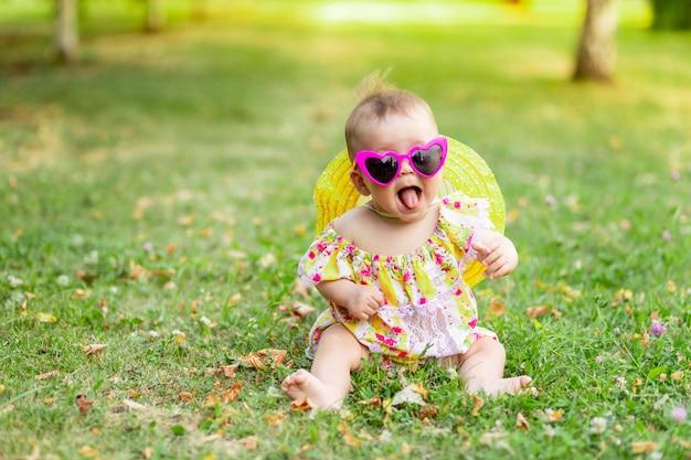 Een klein meisje van 7 maanden zit op het groene gras in een gele jurk, hoed en heldere bril en toont haar tong, wandelen in de frisse lucht. ruimte voor tekst