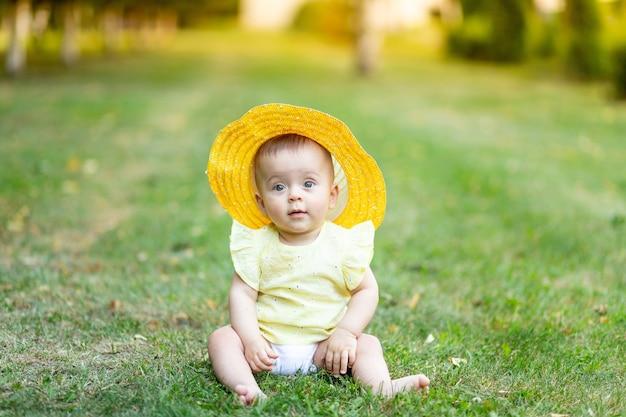 Een klein meisje van 8 maanden zit in de zomer op het groene gras in een gele zomerjurk en hoed