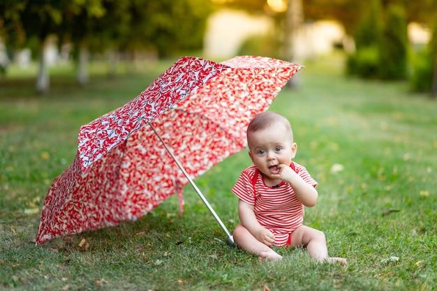 Een klein meisje van 8 maanden zit op een groen gazon in de zomer onder een rode paraplu bij zonsondergang