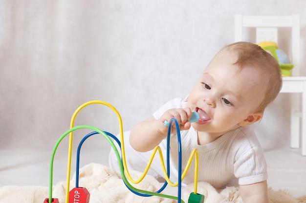 Een klein meisje van acht maanden oud stopt vreemde voorwerpen in haar mond terwijl ze in haar kamer is