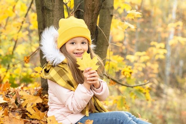 Een klein meisje verheugt zich in de komende herfst.