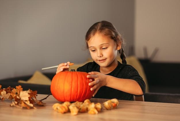 Een klein meisje versiert een pompoen in een kamer voor halloween. kinderen versieren huis. kinderen snijden pompoen. spookachtig halloween-plezier