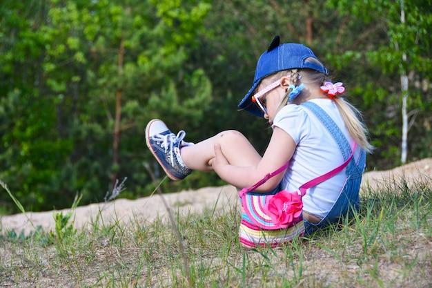 Een klein meisje viel op straat in het veld