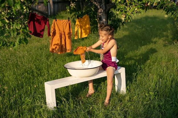 Een klein meisje wast kleren met haar handen in een wasbak zittend op een bankje