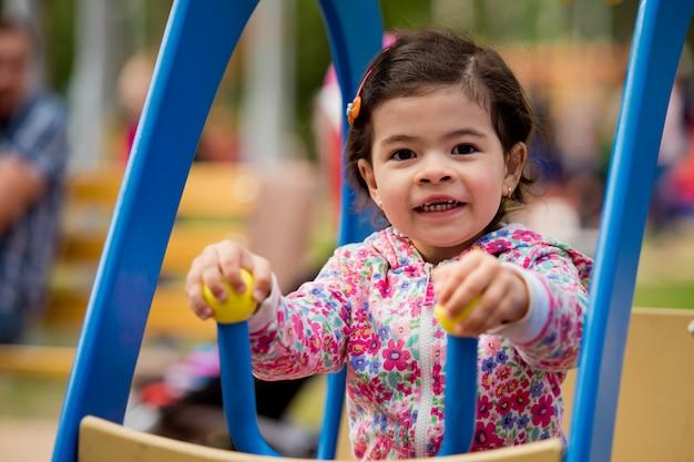 Een klein meisje wordt gegooid over de attracties in het park