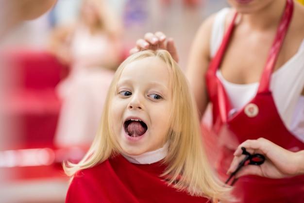 Een klein meisje wordt geknipt