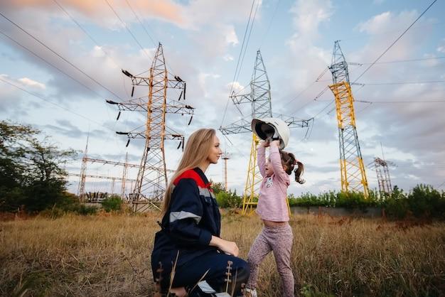 Een klein meisje zet een helm op voor haar moeder voor een ingenieur. zorg voor toekomstige generaties en het milieu. energie.