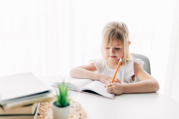 Een klein meisje zit aan de tafel en schrijft huiswerk in een wit notitieboekje. onderwijs, thuisonderwijs concept