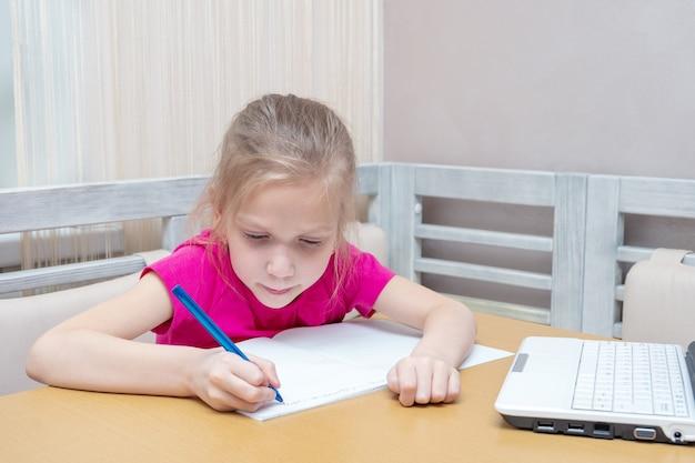 Een klein meisje zit aan een tafel met een laptop en schrijft huiswerk in een notitieboekje