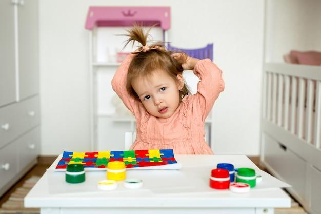 Een klein meisje zit aan een tafel met een tekening en gouache