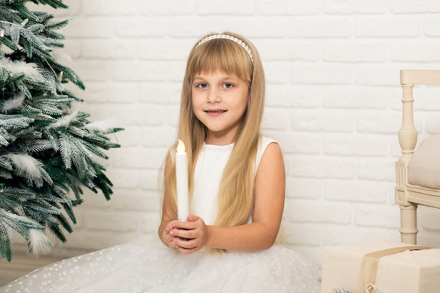 Een klein meisje zit en houdt een kaars in haar hand in een kamer in de buurt van de kerstboom.