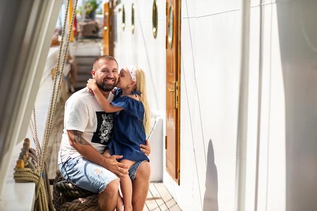 Een klein meisje zit in de armen van haar vader en kust hem op de wang op het dek van een groot litouwen
