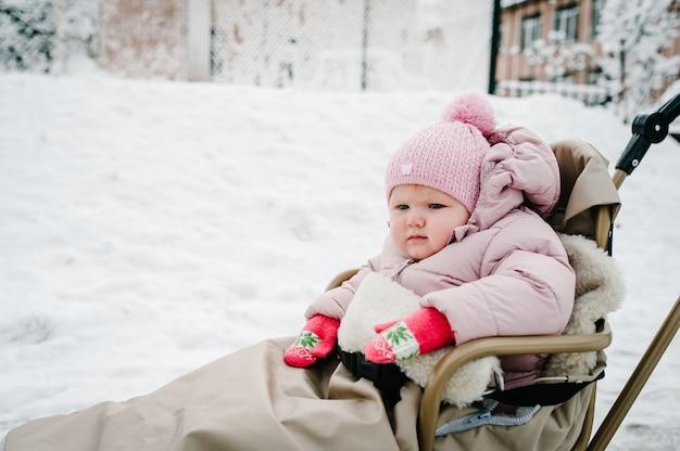 Een klein meisje zit in de slee van kinderen in het park.