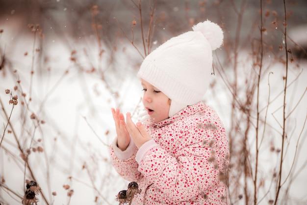 Een klein meisje zit in de sneeuw en verwarmt haar bevroren handen met haar adem