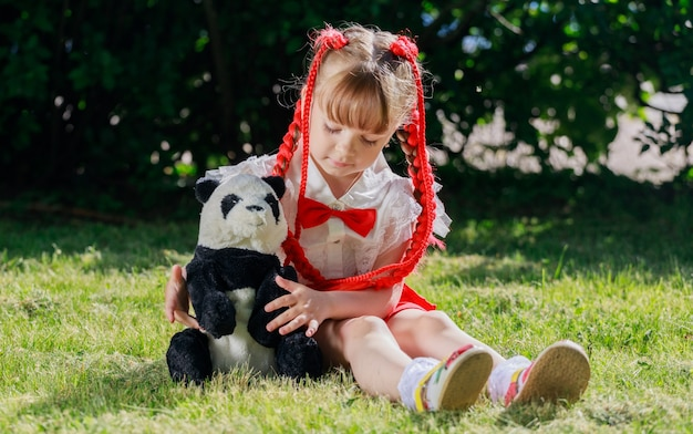 Een klein meisje zit in de zomer in de natuur met een speelgoedpanda. hoge kwaliteit foto