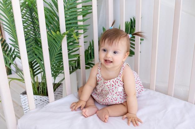 Een klein meisje zit in een lichte kamer in een wieg en glimlacht