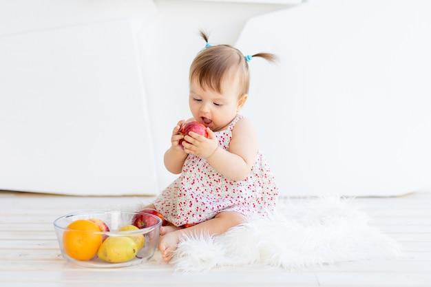Een klein meisje zit in een lichte kamer met een bord fruit en eet een appel