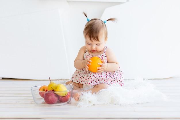 Een klein meisje zit in een lichte kamer met een bord fruit en eet een sinaasappel