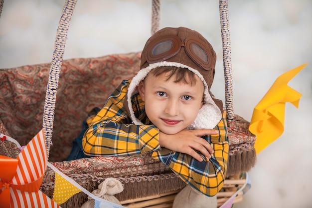 Een klein meisje zit in een mand van hete luchtballon in het park die beweert te reizen en te vliegen met een proefhoed voor een creativiteit of verbeeldingsconcept.
