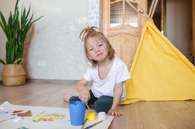 Een klein meisje zit met aquarellen op de vloer en bereidt zich voor om te tekenen. creativiteit van kinderen