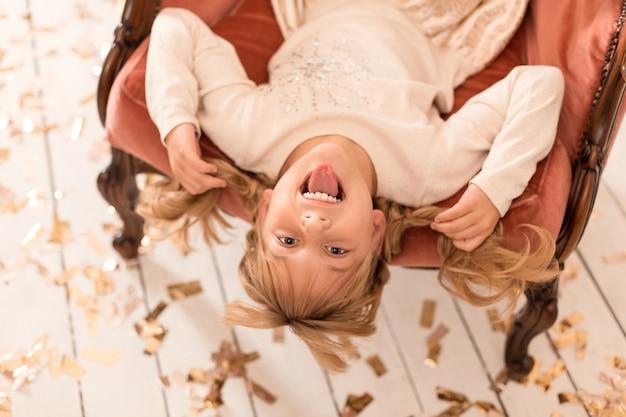 Een klein meisje zit ondersteboven in een stoel. een hyperactief kind.