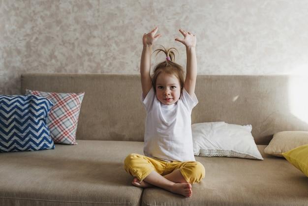 Een klein meisje zit op de bank in een gele broek en een wit t-shirt met haar handen omhoog en doet ochtendoefeningen.
