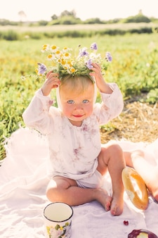 Een klein meisje zit op de grond met een bloemenkrans op haar hoofd en glimlacht
