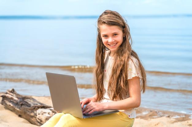 Een klein meisje zit op een boomstam op het strand met een laptop op haar schoot het kind gebruikt een laptop