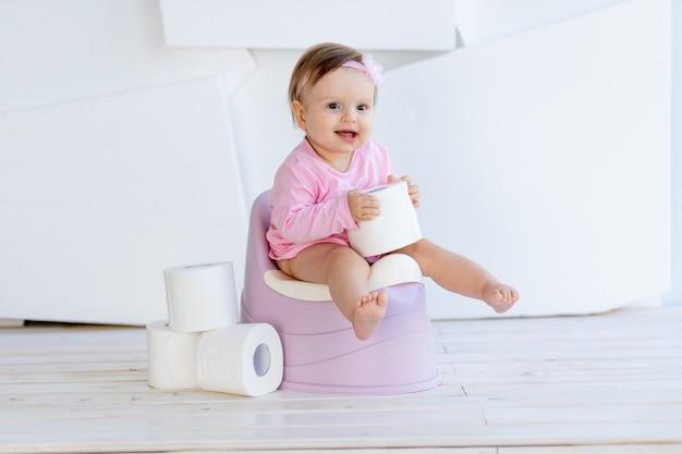 Een klein meisje zit op een potje in roze kleren in een lichte kamer en speelt met wc-papier