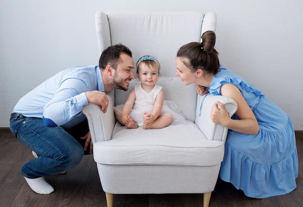 Een klein meisje zit op een stoel, en haar vader en moeder willen haar kussen. de liefde van ouders is van onschatbare waarde.