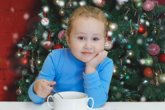 Een klein meisje zittend aan een tafel op de achtergrond van een kerstboom