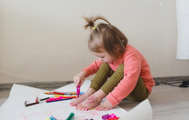 Een klein meisje, zittend op de vloer, geniet van creativiteit, tekenen met potloden kleurplaten in albums.