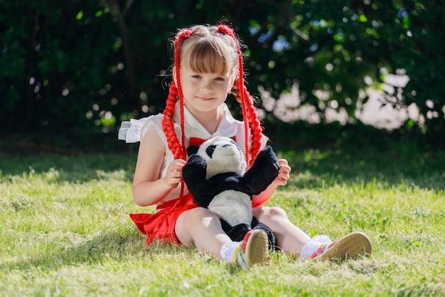 Een klein meisje zittend op het gras in een park met een speelgoedbeerpanda. hoge kwaliteit foto
