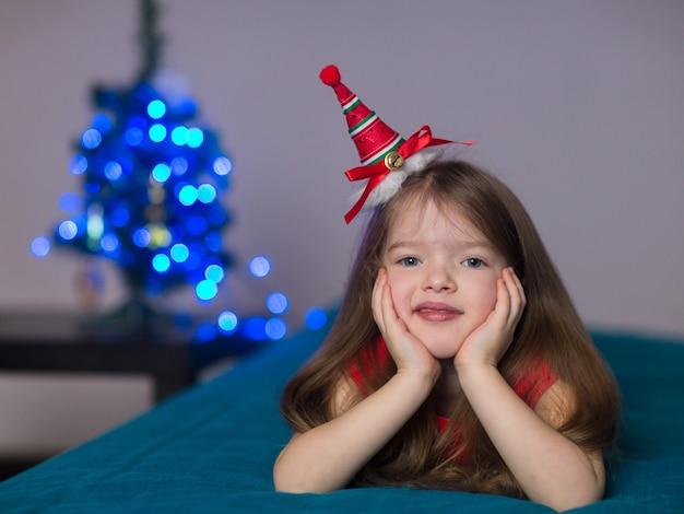 Een klein meisjeskind viert graag kerstmis en nieuwjaar