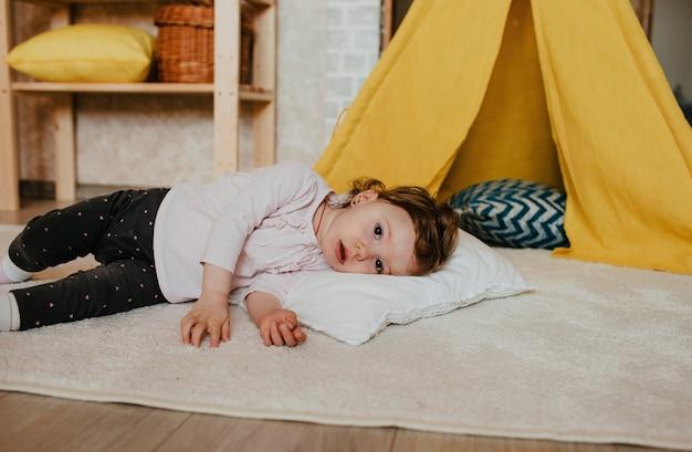Een klein moe meisje ligt op de grond met haar hoofd op een kussen, naast een gele tipi. rust na actieve spellen.