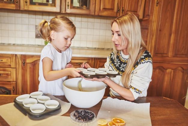 Een klein mooi meisje bereidt cupcakes voor