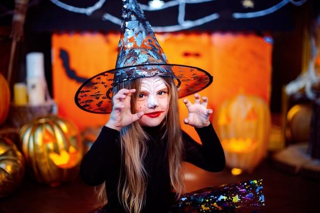 Een klein mooi meisje in een heks kostuum viert thuis in een interieur met pompoenen en kartonnen magisch huis op de achtergrond. schrikt naar de camera.