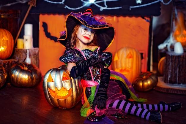 Een klein mooi meisje in een heks kostuum viert thuis in een interieur met pompoenen en kartonnen magisch huis op de achtergrond