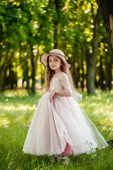 Een klein mooi meisje in een jurk en een hoed in het park glimlacht.