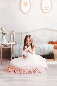 Een klein mooi meisje in een mooie witte jurk speelt met speelgoed op de vloer in de kinderkamer