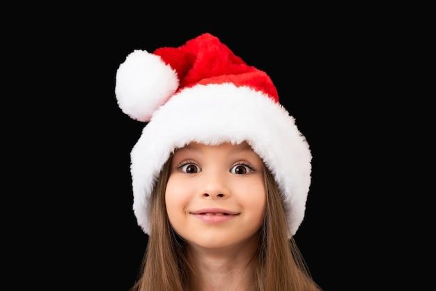 Een klein mooi meisje in een rode kerstmuts vormt.