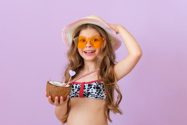 Een klein mooi meisje in een zwempak houdt een kokoscocktail in de ene hand en een hoed in de andere.
