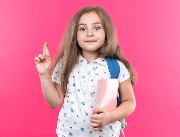 Een klein mooi meisje met lang haar met een rugzak die een notitieboekje vasthoudt, blij en verrast en maakt een wens die de vingers kruist en op roze staat