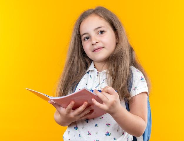 Een klein mooi meisje met lang haar met een rugzak die een notitieboekje vasthoudt en naar de voorkant kijkt glimlachend zelfverzekerd over de oranje muur
