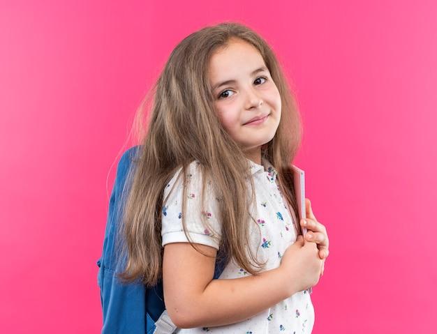 Een klein mooi meisje met lang haar met een rugzak die een notitieboekje vasthoudt en naar de voorkant kijkt met een glimlach op een blij gezicht dat over een roze muur staat