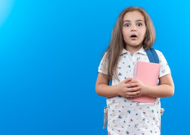 Een klein mooi meisje met lang haar met een rugzak die een notitieboekje vasthoudt en naar de voorkant kijkt verbaasd en verrast over de blauwe muur